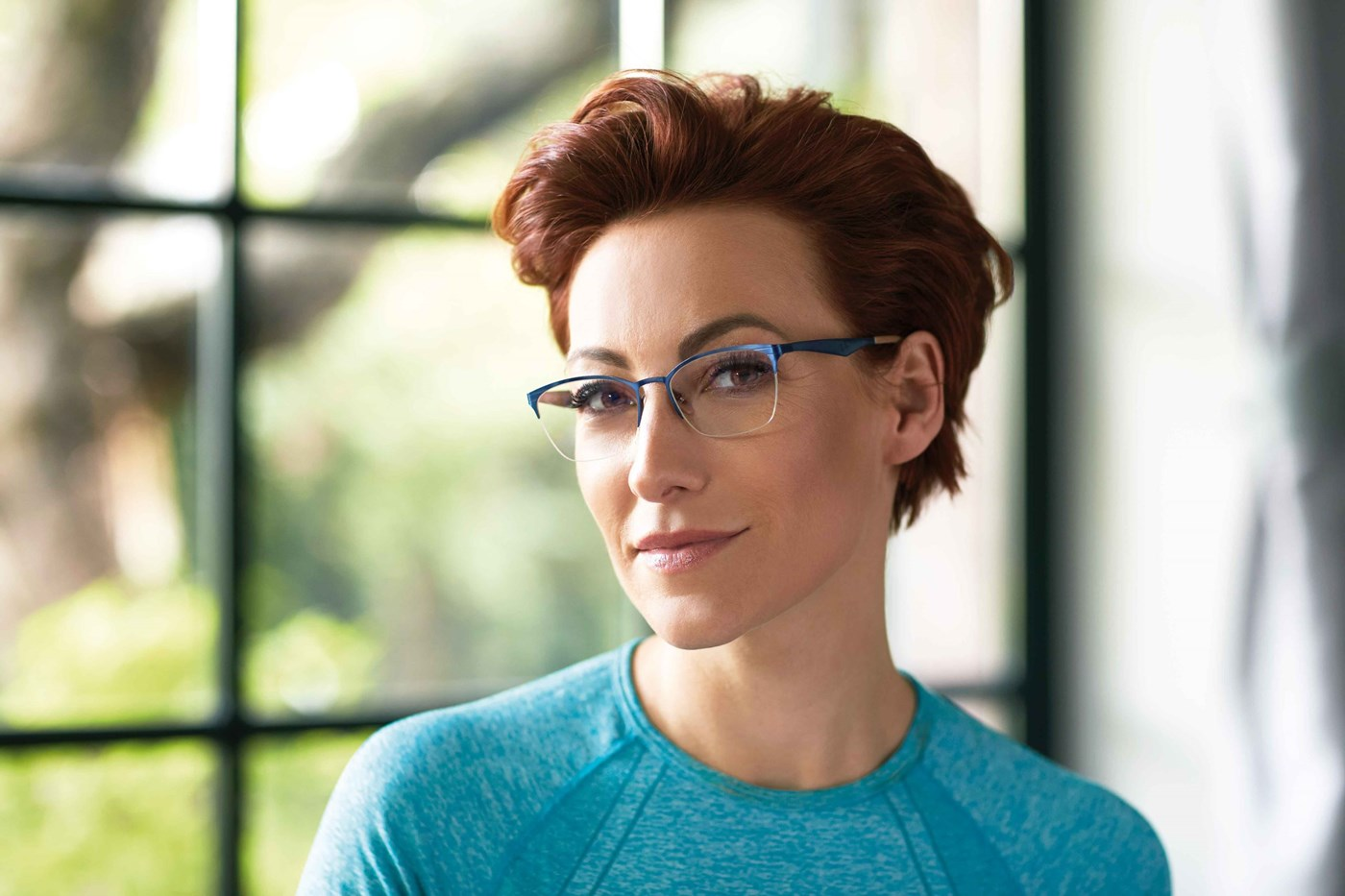 Female in blue top wearing eyeglasses