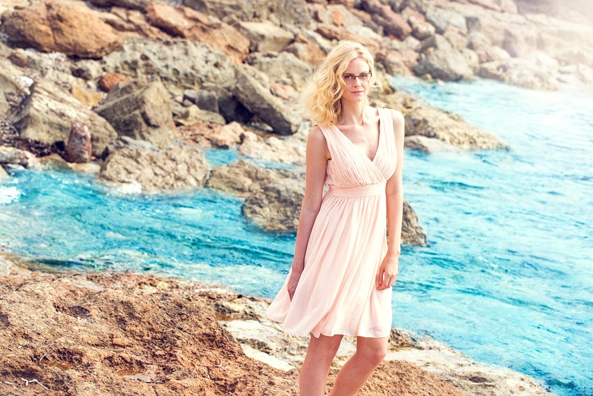 Woman in pink dress wearing eyeglasses on beach beside sea