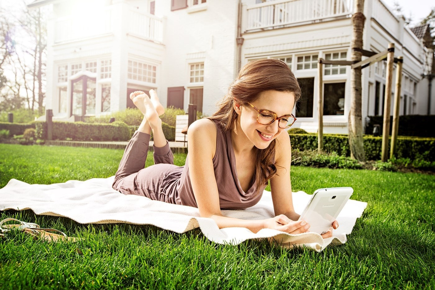Female wearing eyeglasses lying on rug on grass on tablet