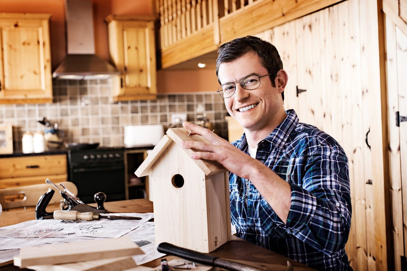 Male wearing eyeglasses building wooden bird house