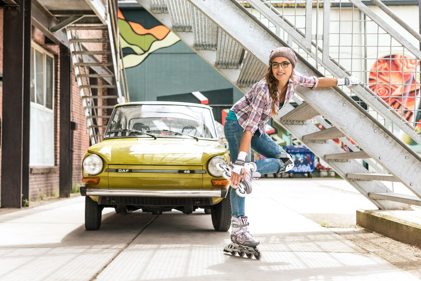 Female roller skater wearing eyeglasses infront of car beside outdoor staircase