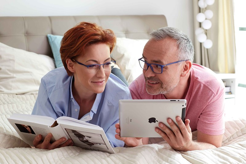 Male holding ipad and female reading book both wearing glasses lying on bed