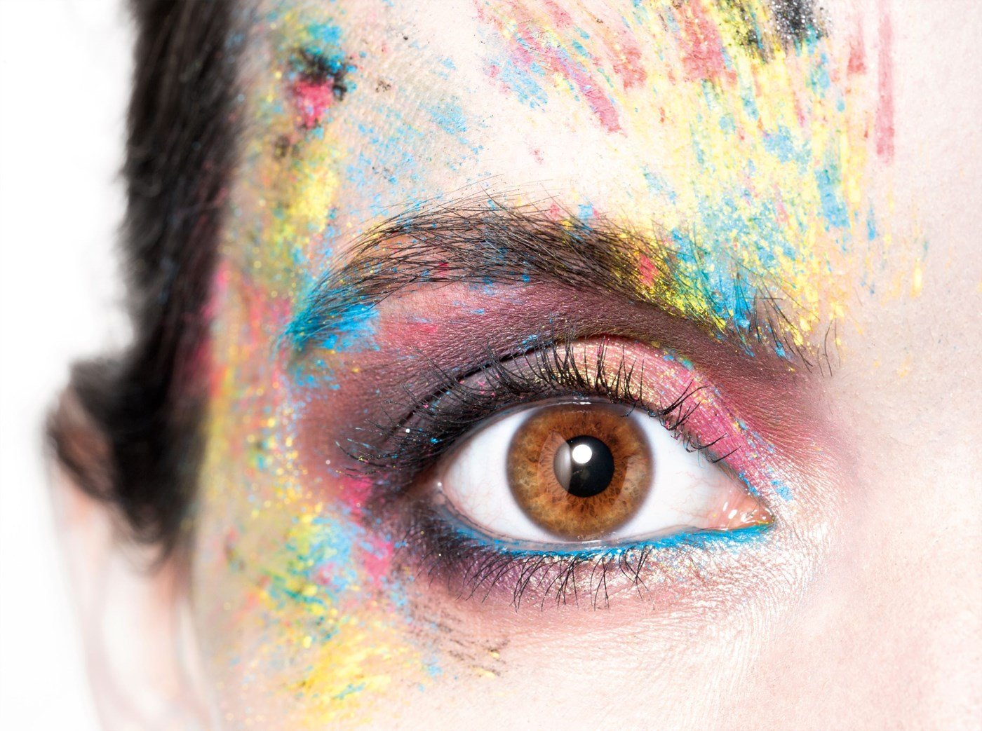 Up close shot of female eye ball with paint splattered over face