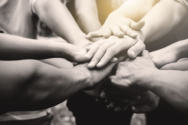 Group of hands in the centre of a circle of people