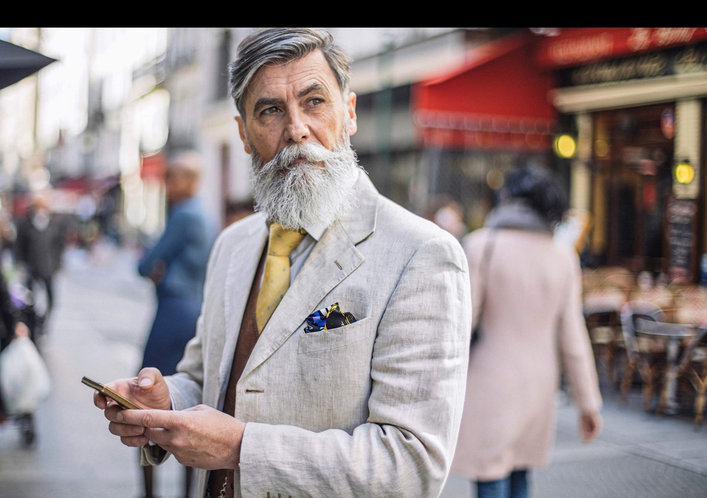 Male with grey beard in suit on a mobile phone